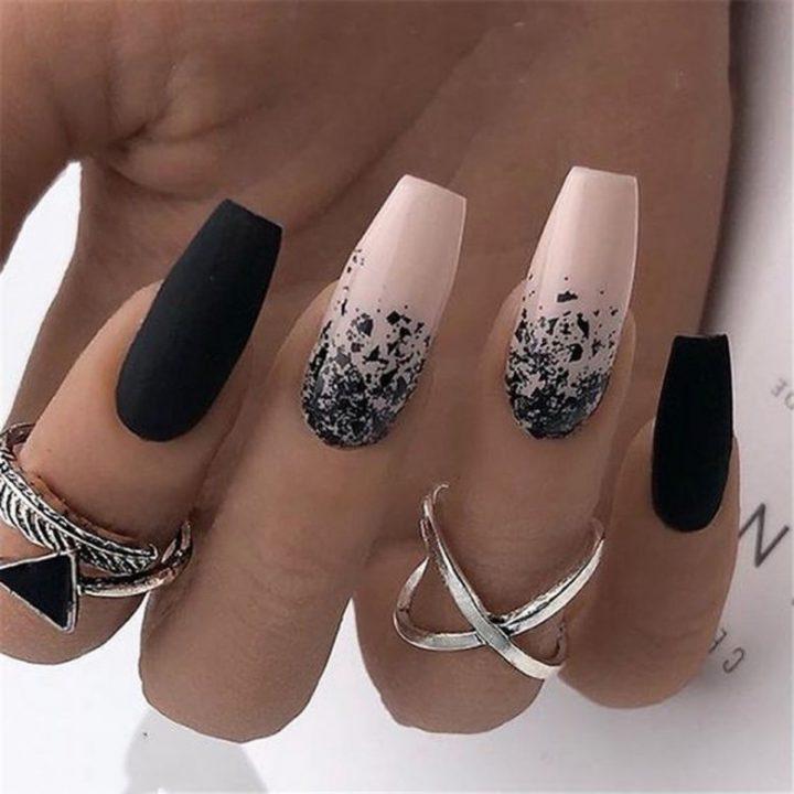 Маникюр в черном матовом цвете с рисунком на длинных ногтях.