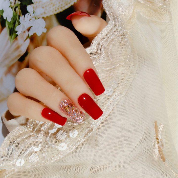 Яркий красный глянцевый маникюр на ногтях квадратной формы.