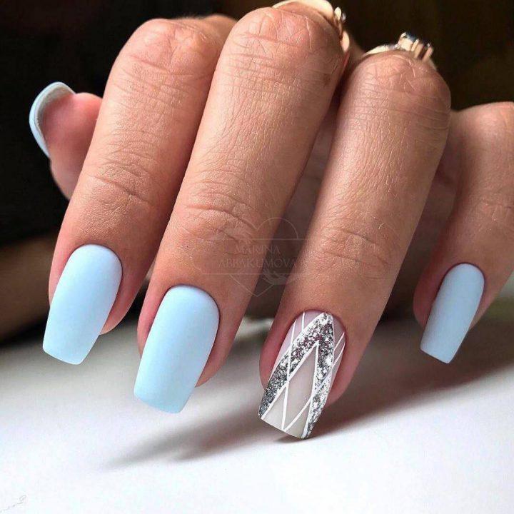 Нежный голубой матовый маникюр с серебром на ногтях мягкой квадратной формы.