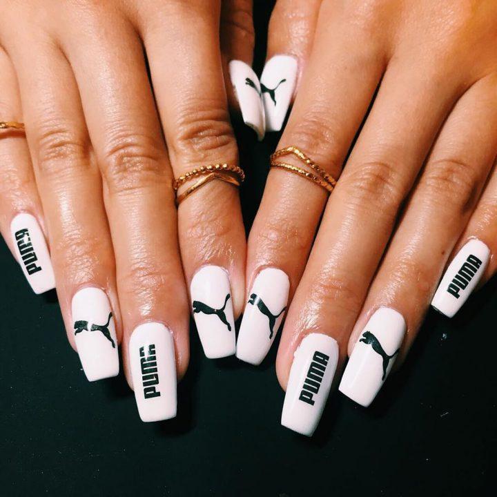 Белый маникюр с надписями на ногтях квадратной формы.