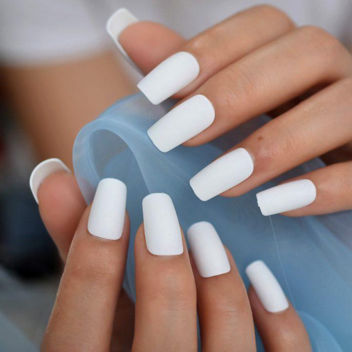 Чистый белый матовый маникюр на квадратных длинных ногтях.