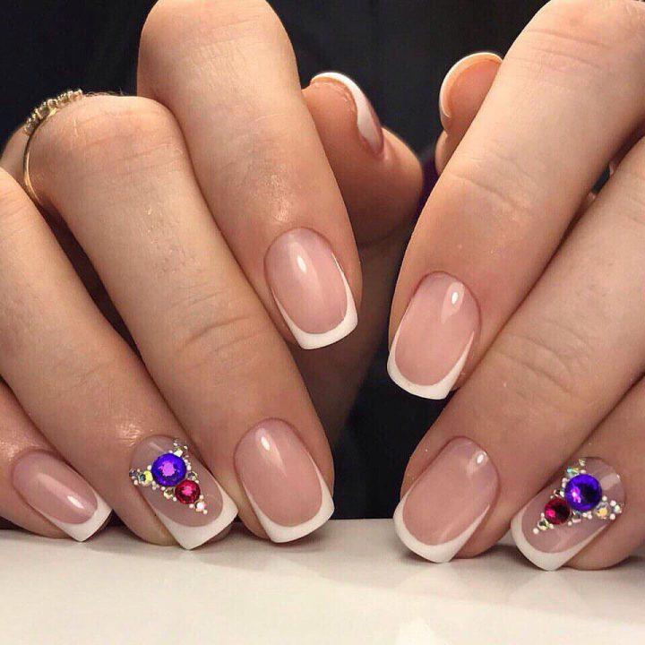 Классический френч на коротких ногтях с использованием крупных цветных страз и мелких страз.
