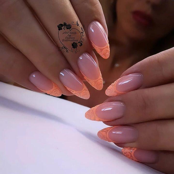 Кружевной персиковый френч на длинных ногтях в форме миндаль.