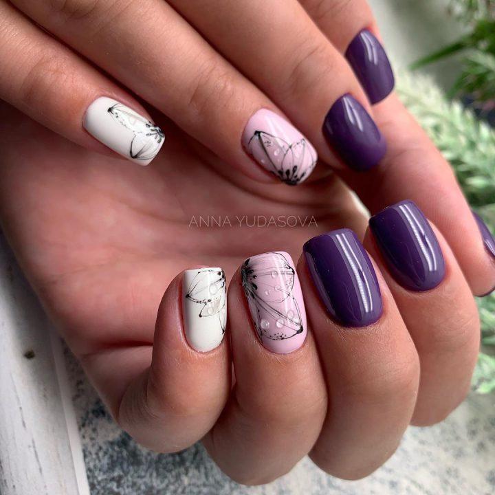 Маникюр модный в фиолетовых оттенках с рисунком на два ногтя и прозрачными капельками.