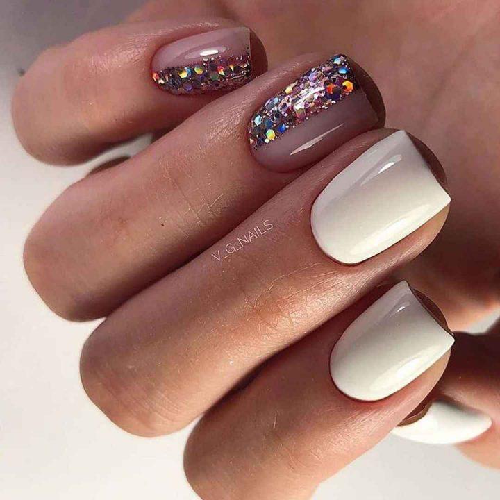 Актуальный маникюр светлых тонов с блестками на половину ногтя.