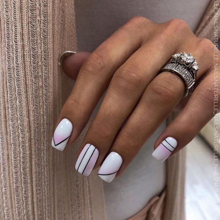 Градиент черные линии на белых ногтях средней длины.