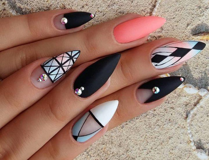 Матовый маникюр на заостренных ногтях миндалевидной формы с стразами и четкой геометрией.
