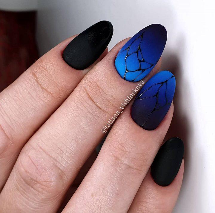 Черный матовый маникюр с синим матовым цветом и рисунком паутинка.