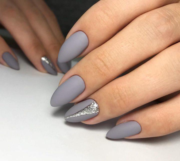 Красивый матовый серый маникюр с серебряным рисунком на миндальных ногтях.