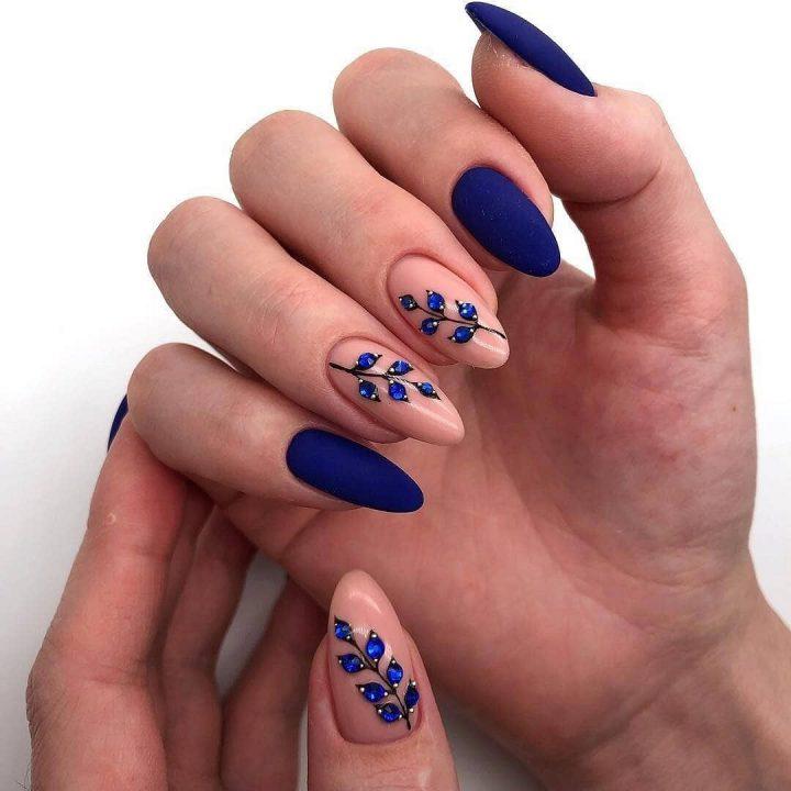 Праздничный синий матовый маникюр с красивыми веточками из страз.