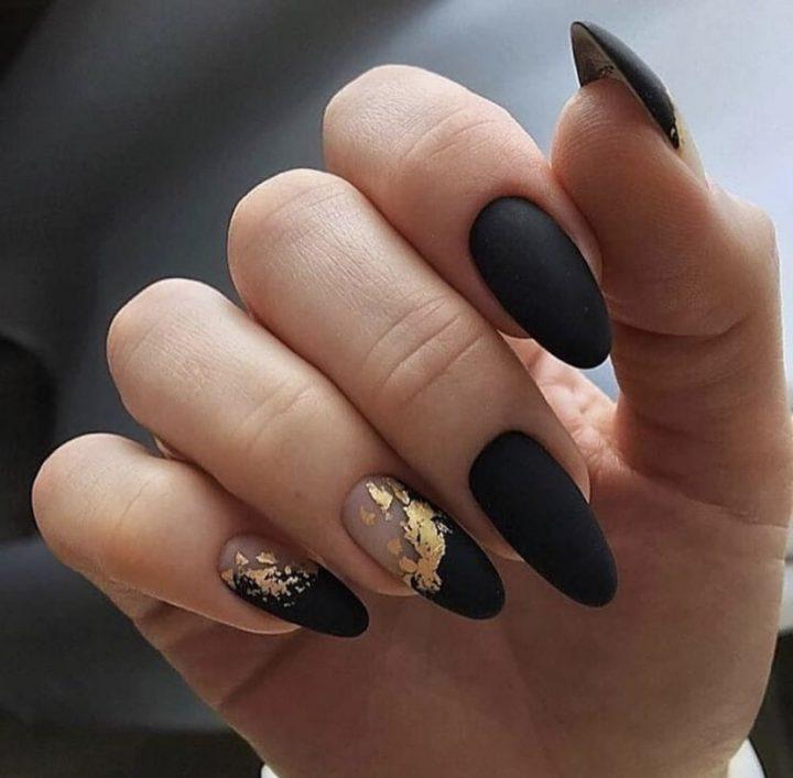 Благородный матовый черный маникюр с золотой фольгой в дизайне ногтей.