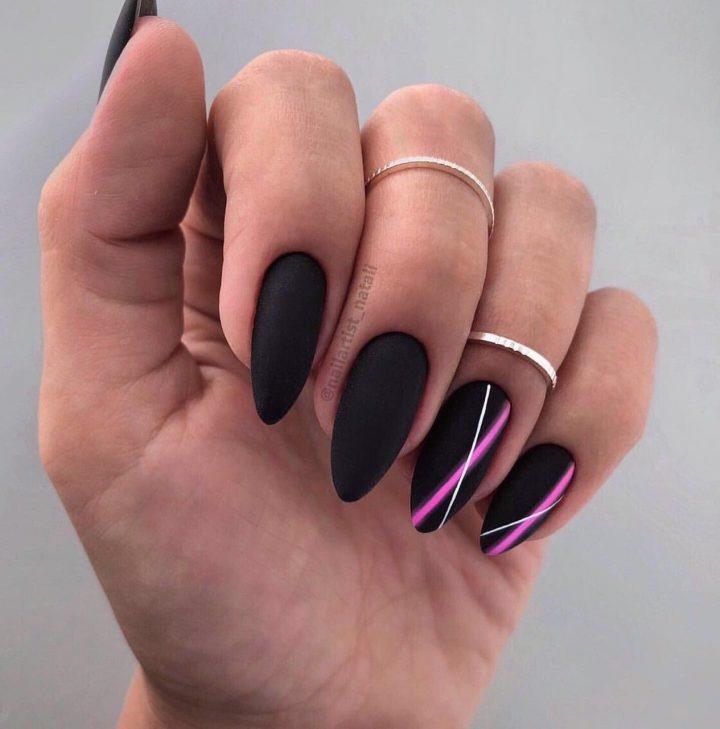 Черный матовый маникюр с неоновыми полосками на аккуратных миндалевидных ногтях.