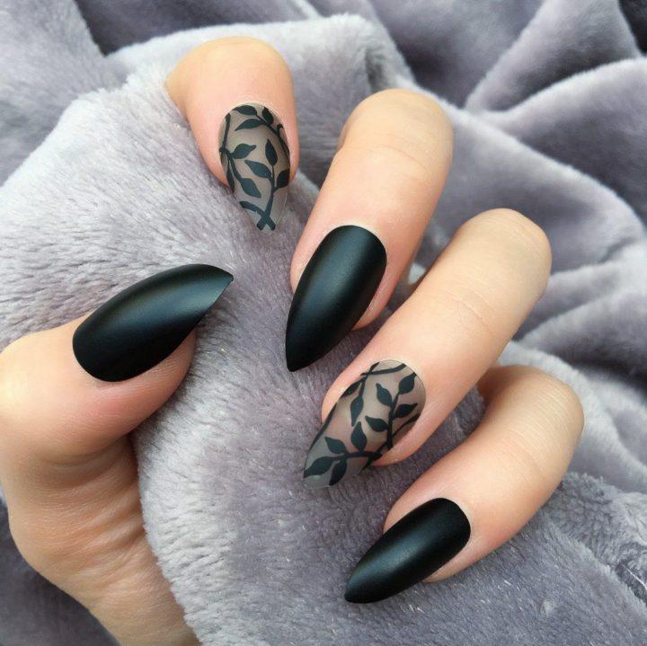 Матовый миндальный черный маникюр с черным риунком на прозрачных ногтях.