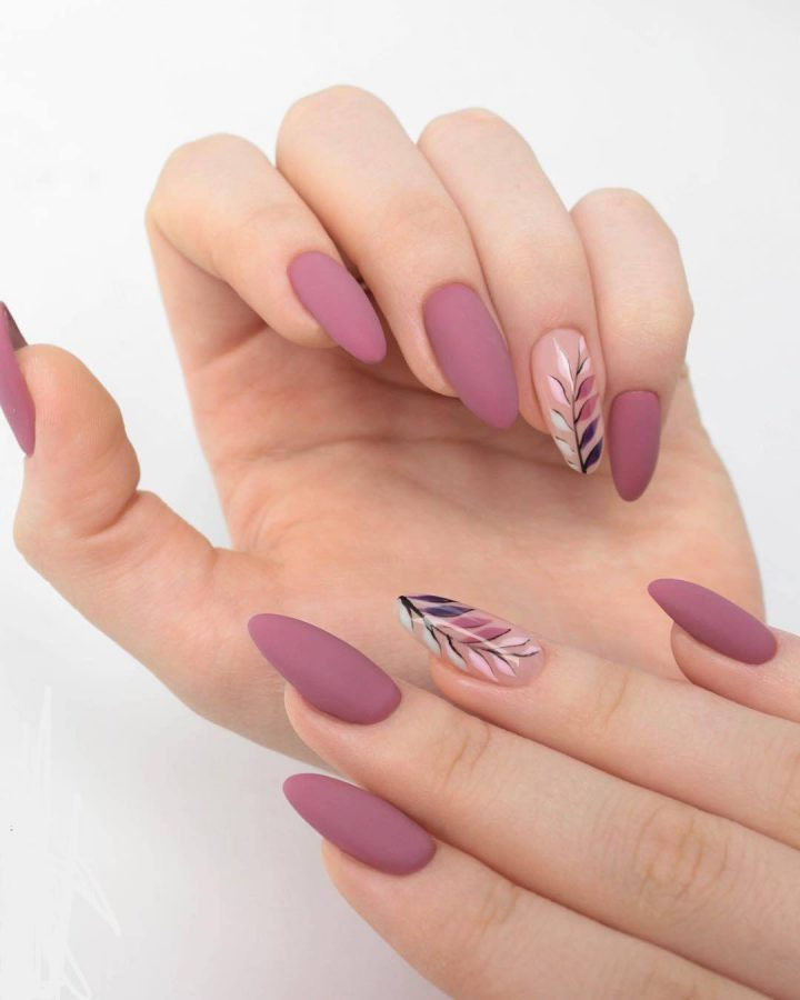 Нежный нюдовый маникюр с красивыми веточками на острых ногтях.