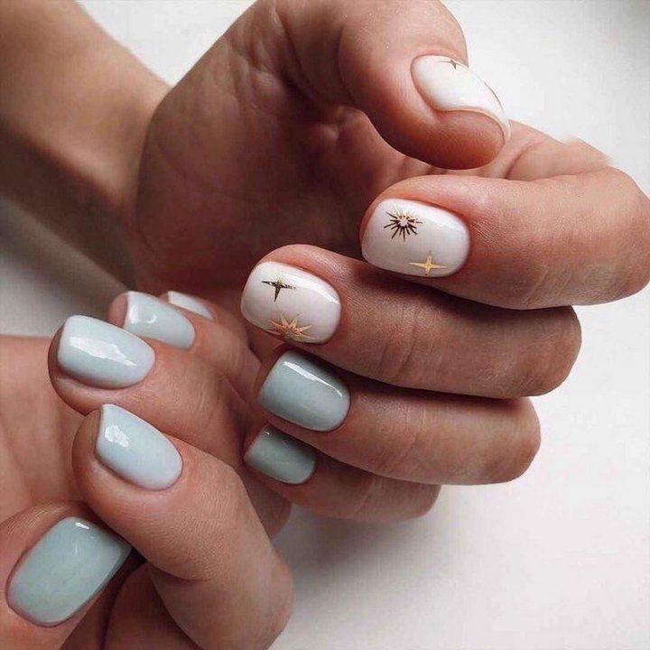 Нежный маникюр в голубых и белых тонах. С рисунком в виде звезд на большом и укозательных пальцах.
