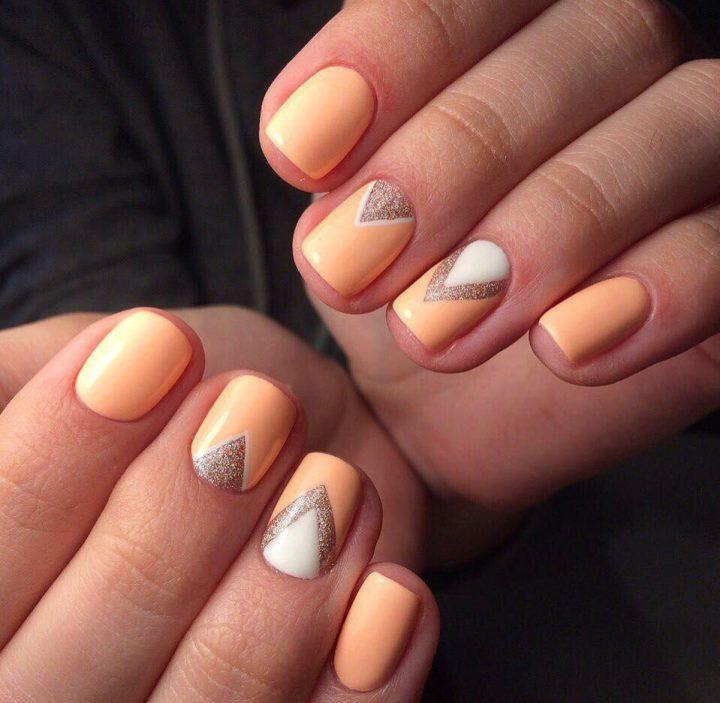 Аккуратный персиковый маникюр с рисунком треугольники на квадратных коротких ногтях.