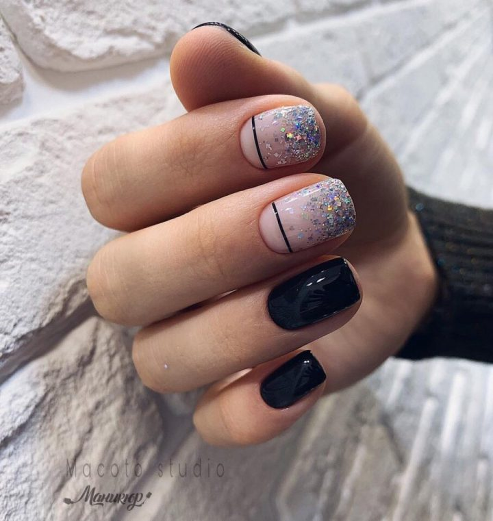 Черный маникюр на коротких квадратных ногтях с акцентом на 2 ногтя в виде блесток на молочном лаке с черной тонкой полосой.