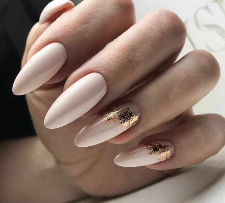 Красивый нежно -бежевый маникюр на длинных ногтях миндальной формы с золотой фольгой.