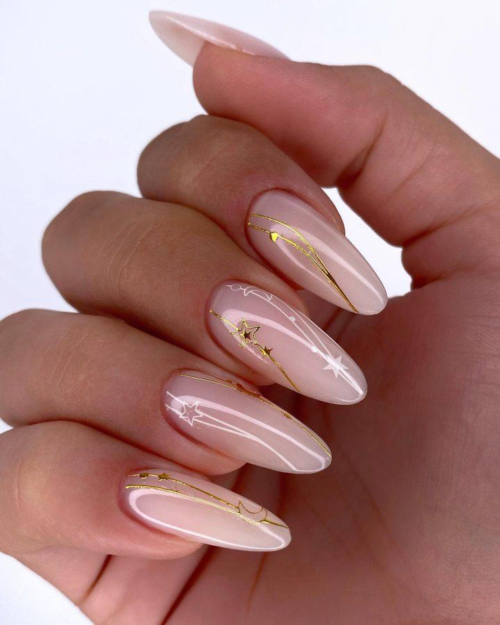 Нежный маникюр с белыми и золотыми звездочками нав длинных ногтях.