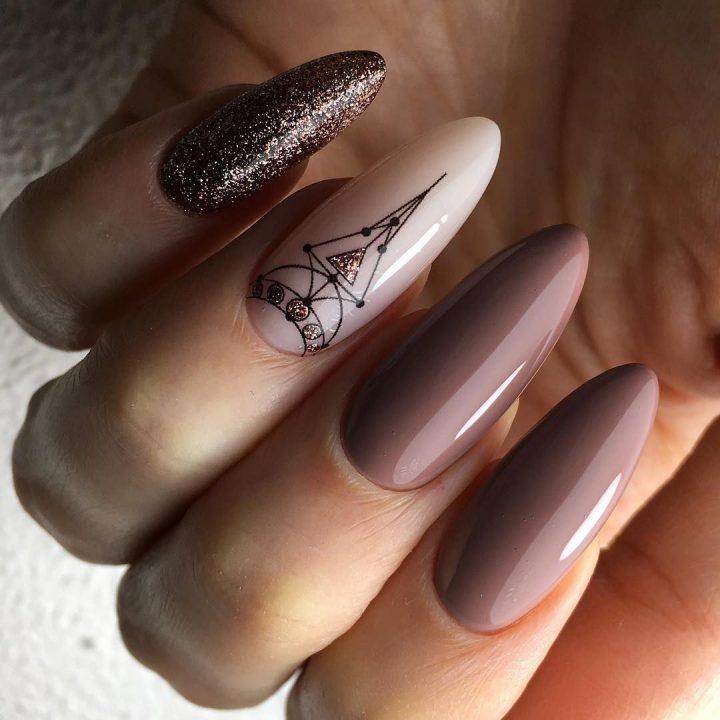 Длинные миндалевидные ногти в коричневом цвете с рисунком и с блестками.