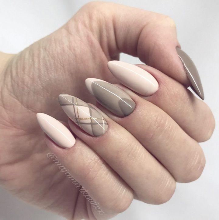 Нейтральный нюдовый маникюр в светлобежевых цветах на ногтях формы миндаль.