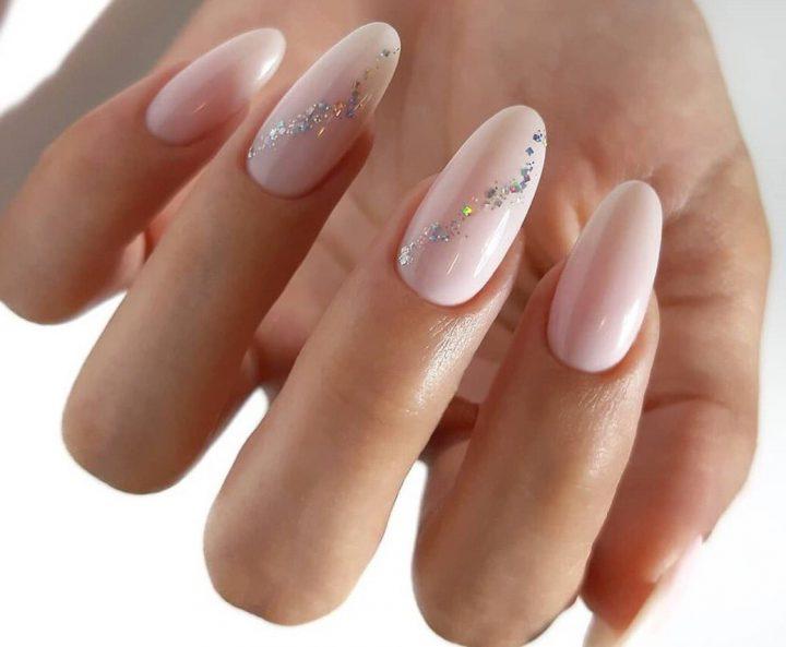 Молочный маникюр с нежными блестками на длинных миндалевидных ногтях.