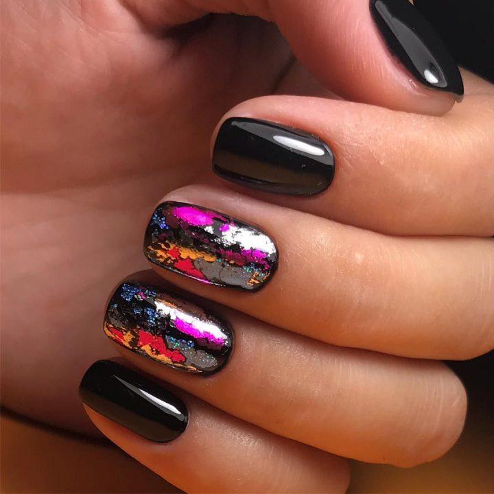 Смелый черный маникюр, разоцветная фольга украшает ногти.