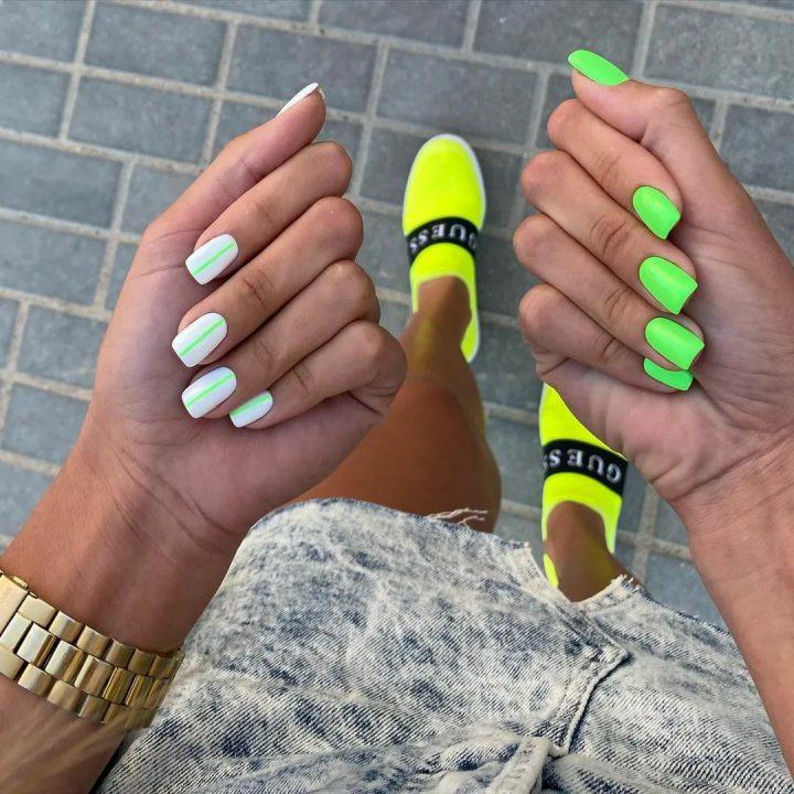 Современный молодежный маникюр яркого зеленого цвета на одной руке, на другой маникюр белого цвета с зелеными полосками.
