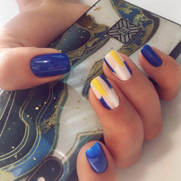 Синий маникюр с ярким рисунком на прямоугольных ногтях.